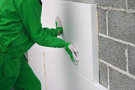 Operario adhiriendo panel a pared con adhesivo de poliuretano Olivé A-45